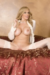 Dressed only in sexy sheer white lingerie, white thigh high stockings and a pearl necklace, beautiful busty blonde, Julia Ann, is looking like a very naughty class act!