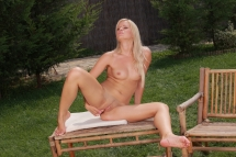 Blonde babe Brigit is fingering her pussy outdoor