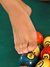 Skinny girl playing biliard balls with her feet