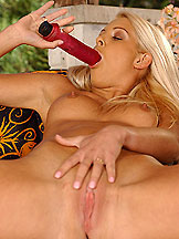 Sexy blonde Pearl is toying a red dildo outdoor