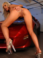 Smiling blonde pornstar dildoing on a red Corvette