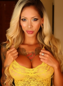 Alluring Vixens: Busty tattooed babe Chanel shows off her huge tits in a skimpy yellow lace outfit