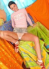 Sweet looking teenie girl plays with a big toy on her bed