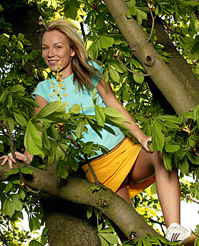 Blonde teenage cutie shows her tight pussy in a big tree