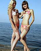 Two young teen nudists showing their fit body on the beach