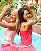 Two very hot teenage girls playing with hula hoop at pool
