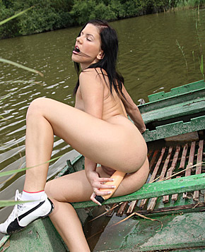 A hot naked chick posing on a boat in the water for camera
