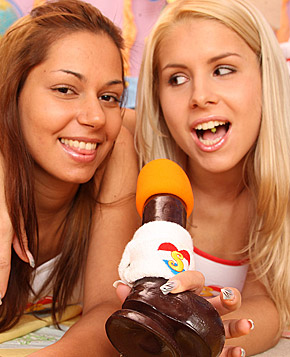 Two hot lesbian teenagers singing karaoke with a big dildo