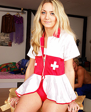 A sexy teenager wearing a nurse outfit undresses completely