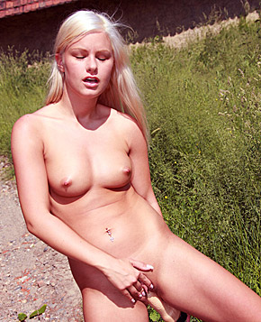 A pretty blonde playing with herself on the road in the nude