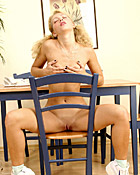 A very sexy blonde with pigtails posing naked on a chair