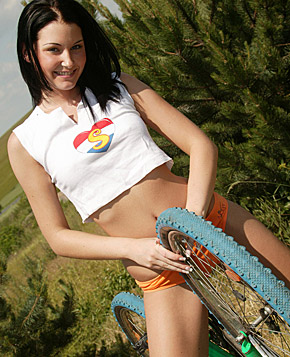 Hot teenage cutie on a bike masturbates near some bushes