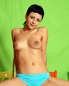 A naked teenage girl with short hair plays with herself