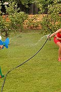 Two hot lesbian babes playing with a garden hose outside