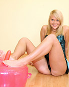 A young teenage sweetie playing with a pink blowup dildo
