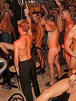 Gay men having a huge group sex orgy party in a dance club