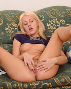 Teen blonde on a couch caressing her tight soaked cooch