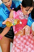 two hot brunette lesbian babes playing with bottles of oil