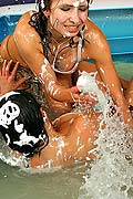 Two sexy lesbian babes wrestling in a small pool of water