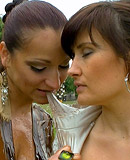 Two cute clothed hotties playing with liquid food outdoors