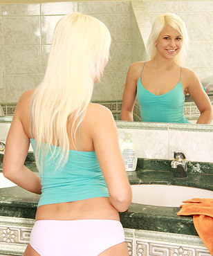 A very blonde babe in the bathroom loves stroking pussy