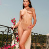 Ravishing siren enticingly strips and poses on the balcony
