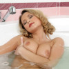 Watch as big breasted beauty bares all in a bubble bath