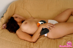 A pretty teenage chick playing with a cute fake penguin