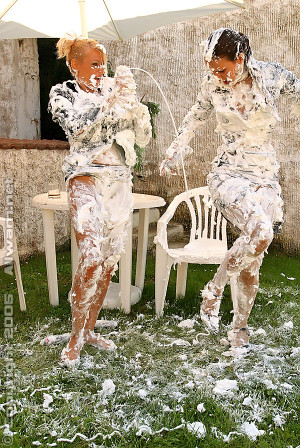 Two sexy babes spraying shaving cream on each other outside