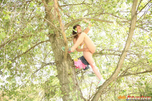 Bikini wearing chick loves playing in a big tree outdoors