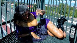 Daring sweetheart spraying water on her clothes outdoors