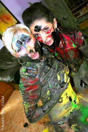Two pretty hot clothed girls playing with loads of paint