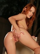 Fiery redhead strips and fists her own bald pussy in garden