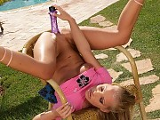 Sizzling siren thrusts big dildo into pussy and ass on lawn