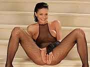 Vixen in fishnet outfit spreads and rubs twat on stairs