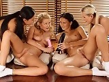 Four stunning ladies undress and fuck dildos on the floor