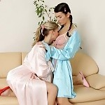 Gorgeous sirens shed nightgowns and lovingly kiss on couch
