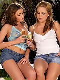 Dazzling honeys kiss and pour wine on hot bodies on patio