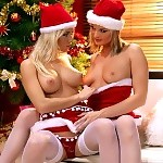 Stunning vixens in Santa outfits kiss and have sex on couch