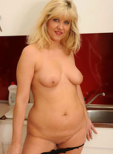 Doreen slips off her jeans and reveals her sexy mature pussy in the kitchen