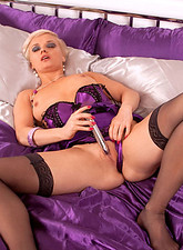 Desirable blonde cougar Natalie drills her starving pussy with a silver vibrator on her bed