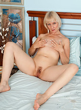 Blonde milf undresses and satisfies her pussy with her fingers