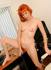 Sasha Brand  Hot redheaded cougar satisfies herself with a dildo while doing her daily tasks in the office