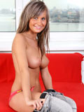 Alluring Nubile Annik pops out her juicy amateur tits before she gets all naked on the sofa