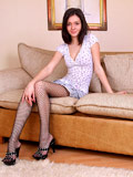 Petite teen in fishnet stockings strips and spreads her legs revealing her pussy