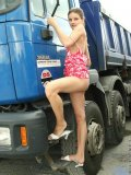 With her hair tied back carolina poses outside infront of a big ass mack truck ooh small boobies