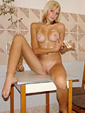 Denisa putting a cream her body then posing nude on top of table