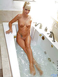 Irresistible Nubile blonde soaks in the bathtub and teases her shaved pussy