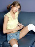 Melody wears knee hight socks and cutoffs while sprawling out on the couch