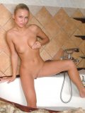 Cute teen gets nice and wet and slippery in the bathtub spreading and playing
